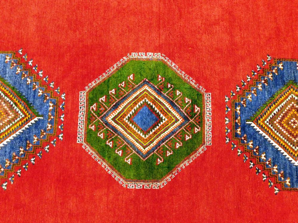 """RUG: Vintage Moroccan rug, 13' 4"""" x 9' 9"""", open brick red field with three latch hook geometric medallions in green and blue, three.."""