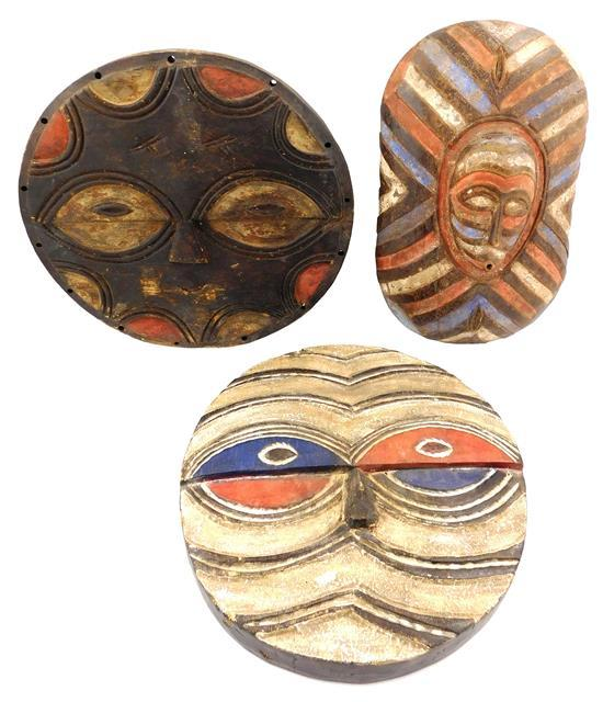 TRIBAL: Two Teke style masks and one Songe type shield, 20th C., wood with carved geometric decoration and polychrome painted finish...