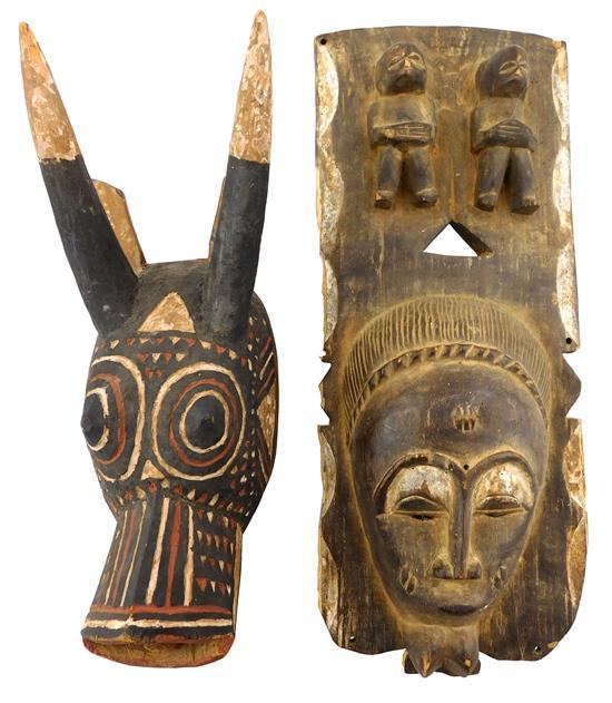 TRIBAL: Two African carved wood masks made for the tourist trade, one Bobo style and one Baule style, details include: oblong Baule...