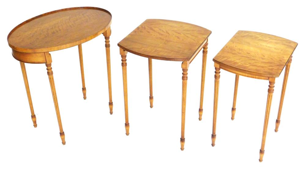 Nest of three Federal style oval top stands, satinwood veneer, fluted legs, largest table has oval top, two smaller rectangular form...
