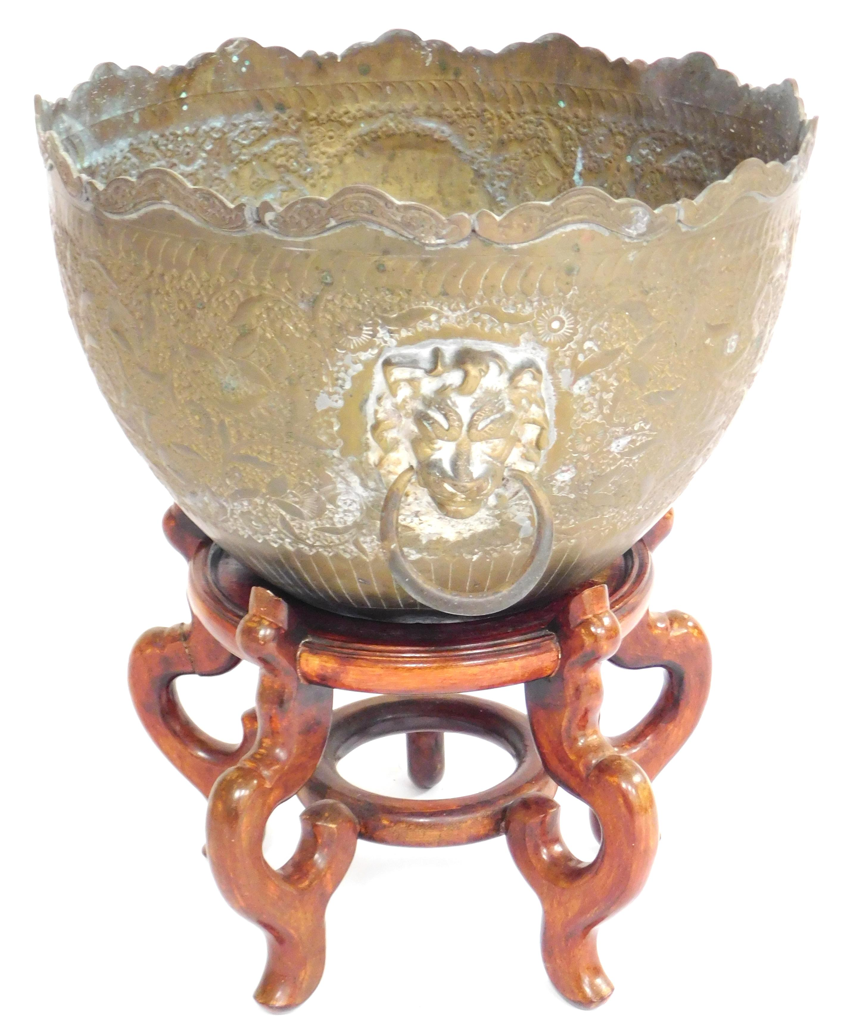 ASIAN: Brass planter and five-legged wooden stand, planter decorated with lion head loop handles and stylized flowers, some corrosio...