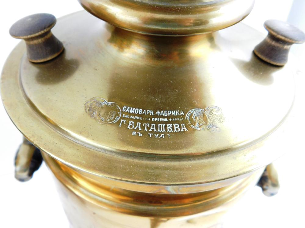 Two Russian brass samovars, late 19th/ early 20th C., ringed top with removable parts, each with two hinged wood carved handles, fro...