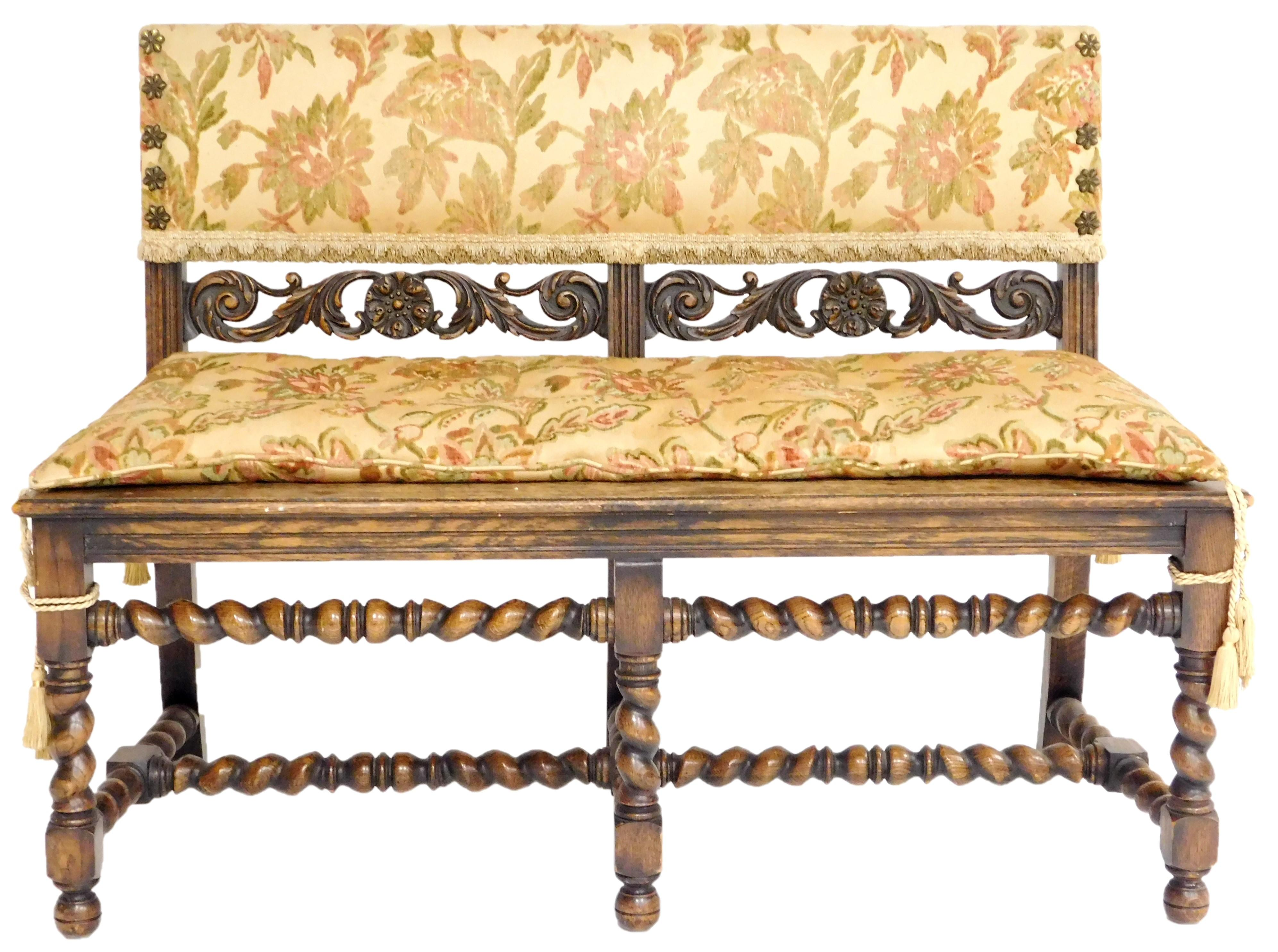 Renaissance style bench with upholstered back rest in tan floral pattern over carved and pierced scroll splat, oversized flower form...