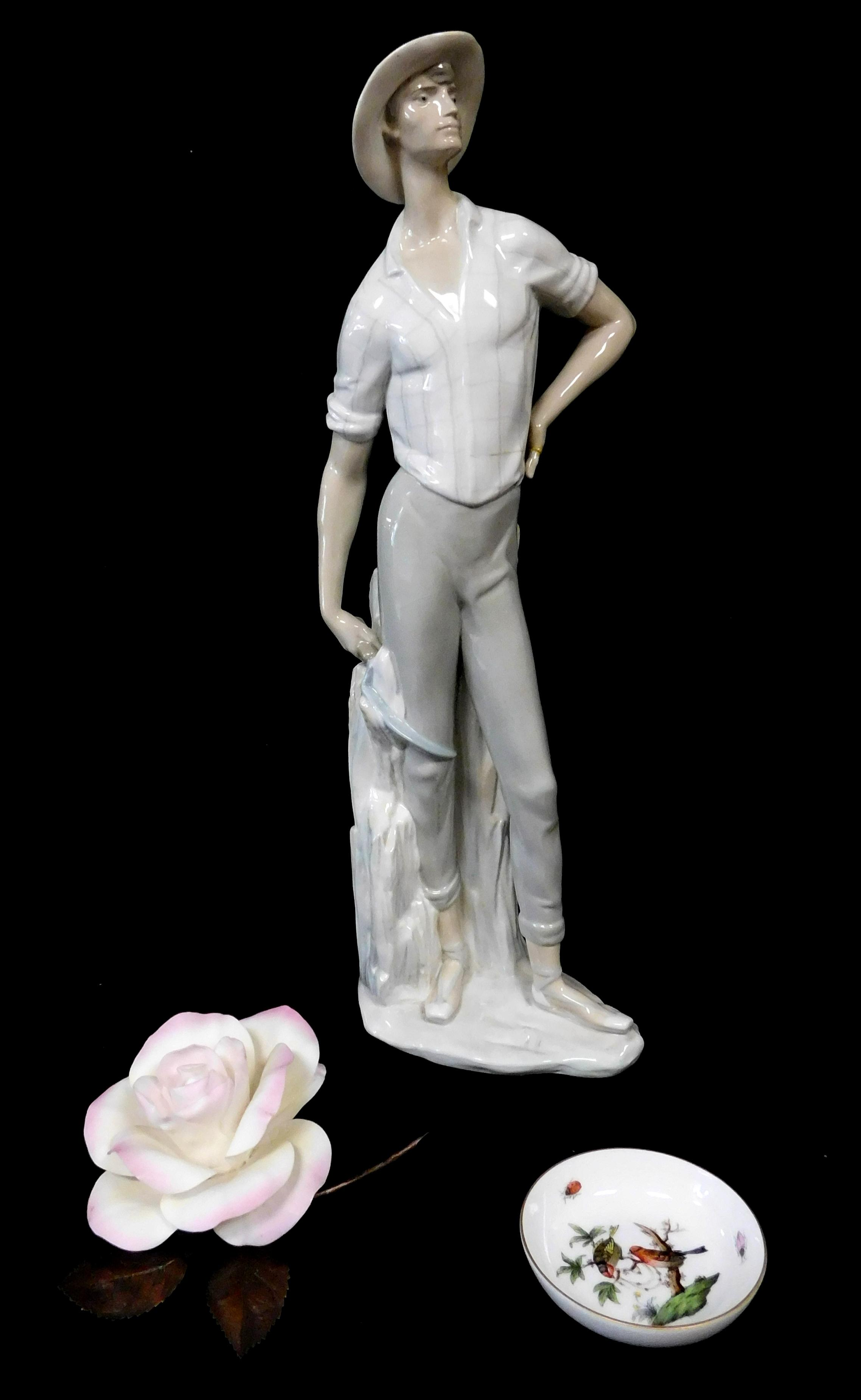 Three porcelain pieces, including: Lladro figure of man with hat and scythe, light slate blue and tan coloring, scattered cracking a...