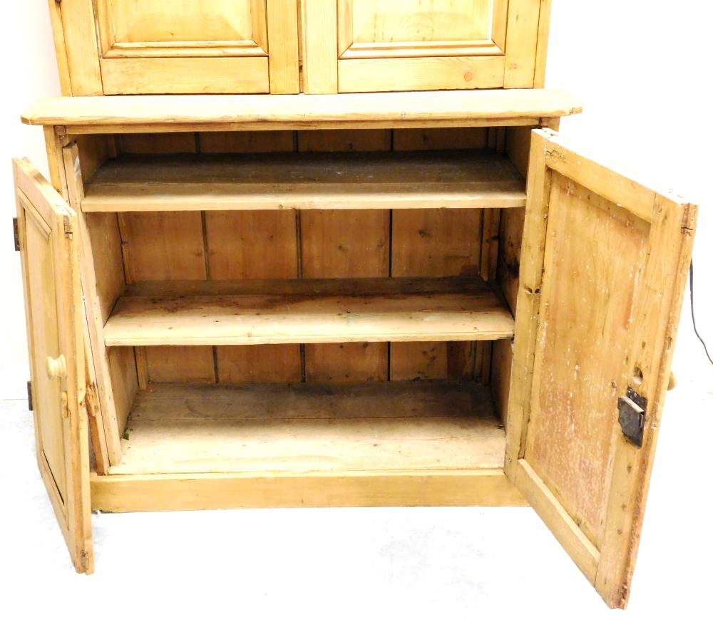 Anglo-Irish pine cabinet with peaked crest, early to mid-20th C., two shaped upper cabinet doors open to reveal three fixed shelves,...