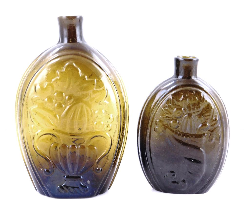 GLASS: Two Cornucopia/urn flasks, G111-4 and a GIII-7, American 1825-1835, olive amber pint and half pint, open pontil, sheared and...