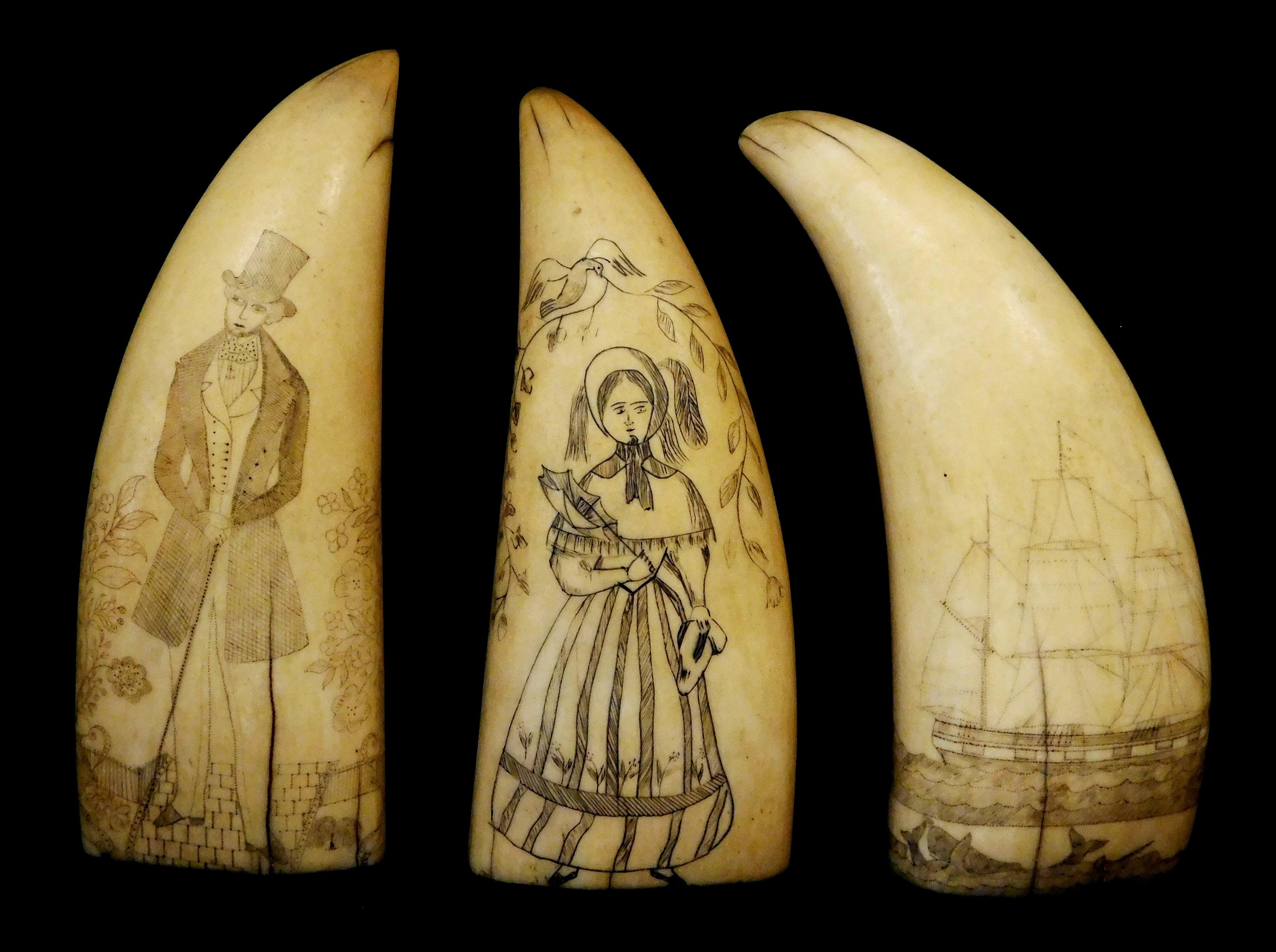 Three scrimshaw decorated sperm whale teeth, featuring a man, woman, and whaling scene with boat and many whales with accents of red...