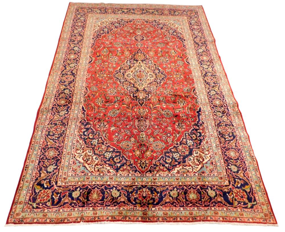 "RUG: Semi-Antique Persian Kashan, 9' x 13' 2"", soft red field, ensconced in wide navy floral border, sky blue guard borders, gold, r."