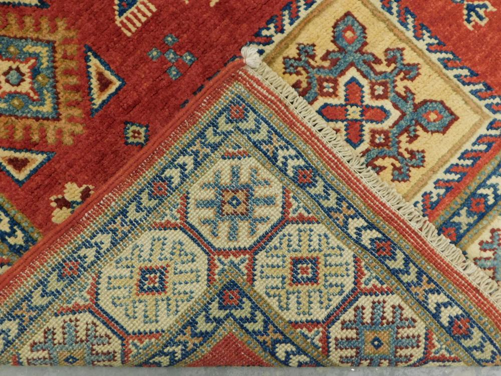 "RUG: Uzbek Kazak, 3' 2"" x 5', red field ensconced in unusual sand colored border, accents of royal blue, teal, cream, gold, garnet."