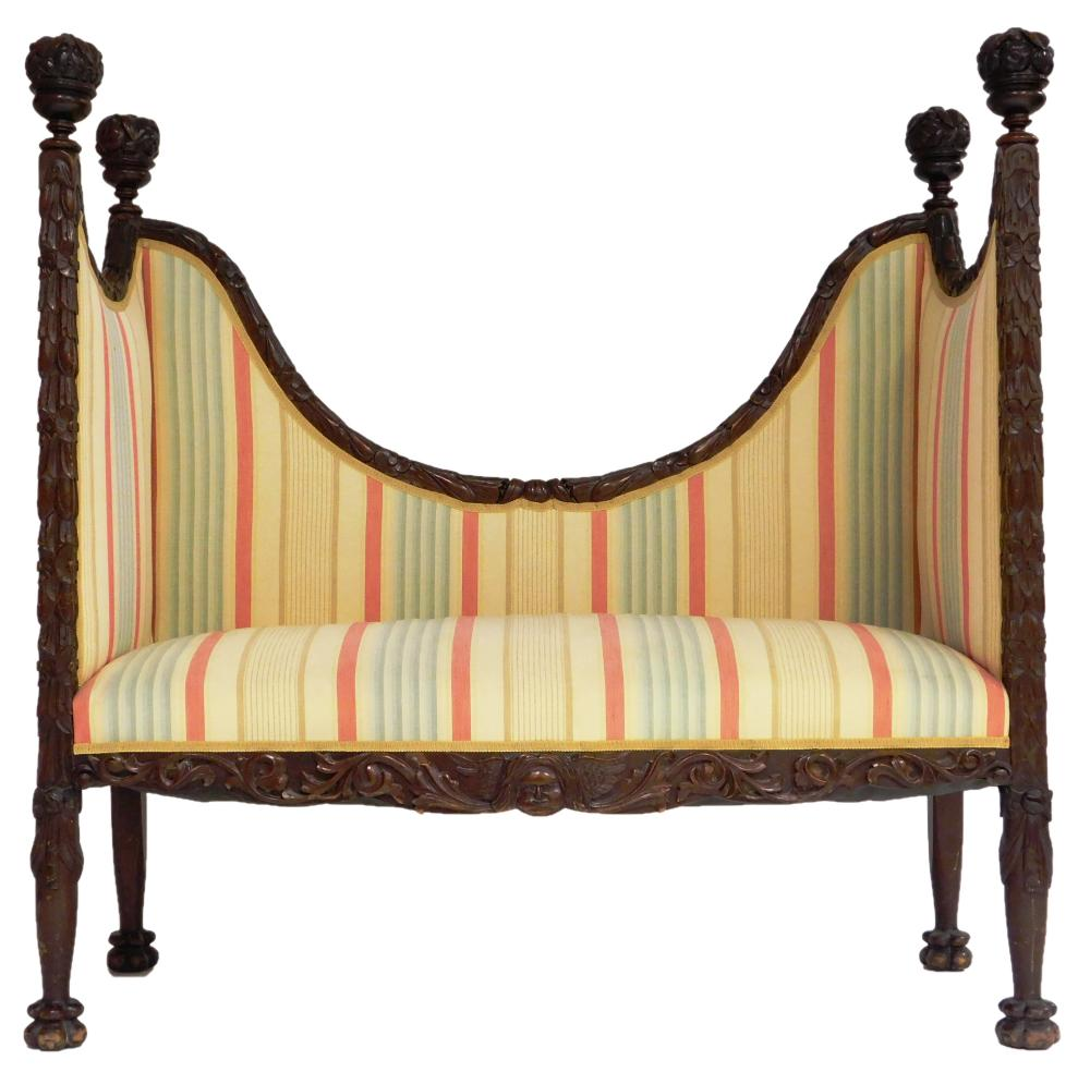 Carved wood settee, floral carvings throughout with tapered legs atop flower bud feet, large floral globes on top, upholstery is yel...