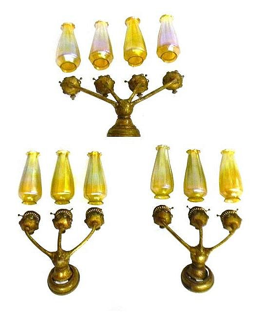 Tiffany set of three sconces, circa 1910, bronze dore supports with turtleback glass jewels: pair of three-light and one four-light,...