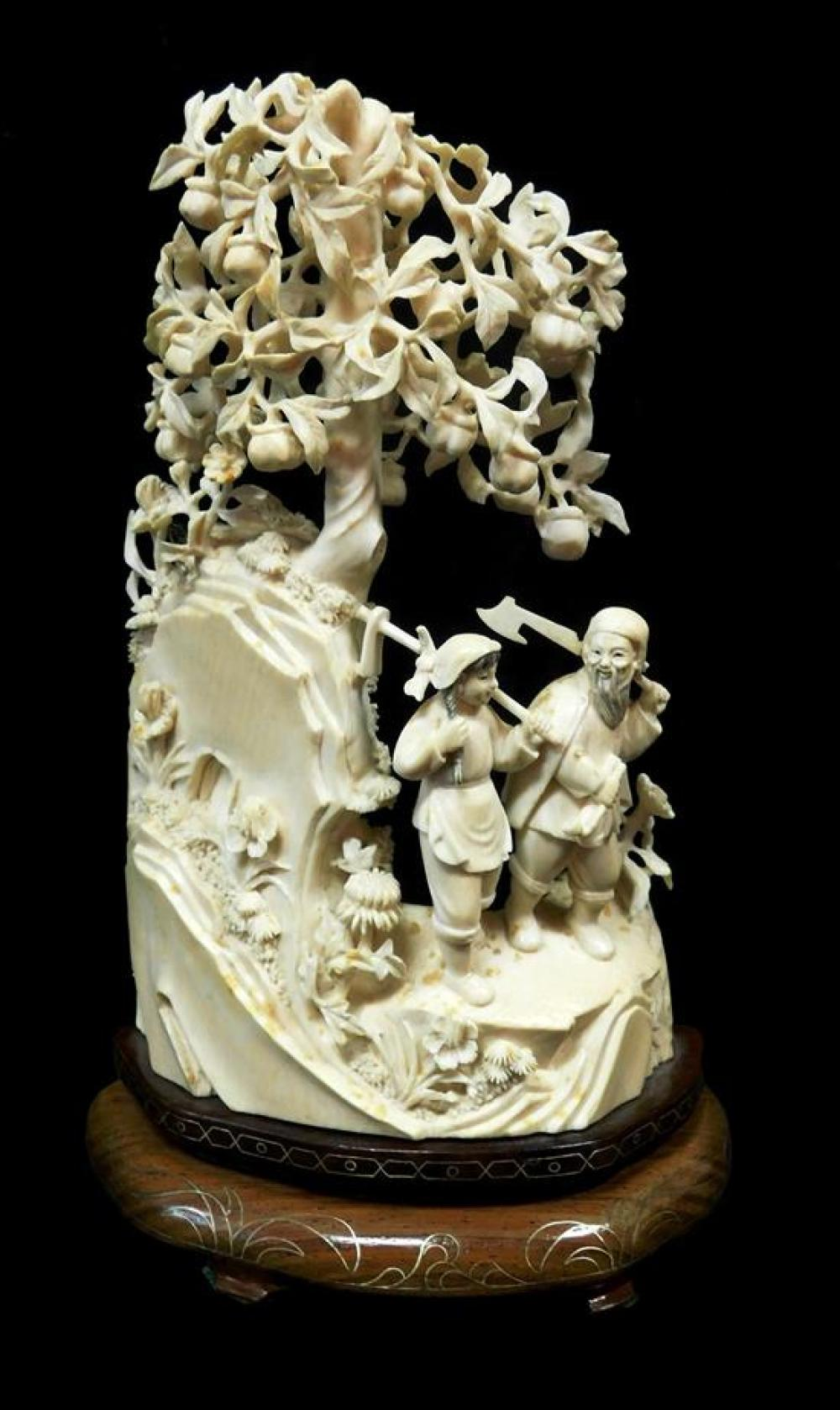 ASIAN: Ivory carving, probably Chinese, Qing Dynasty, early 20th C., modeled as two figures walking on a mountain site beneath a fru...