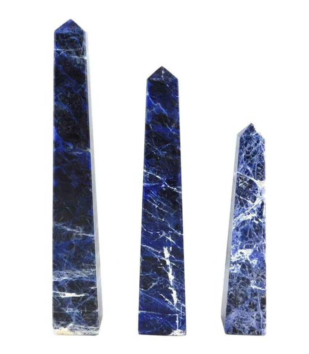 "Three sodalite obelisks, all with rich blue color and white veining, wear consistent with age and use, largest: 14"" h."