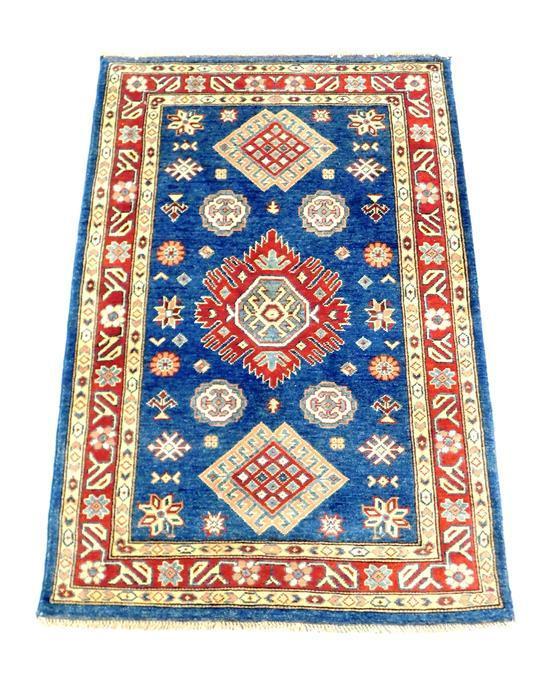 "RUG: Uzbek Kazak, 3' 3"" x 4' 9"", hand-woven, 100% wool, classic geometric design, deep blue ground with central medallions, merlot c."