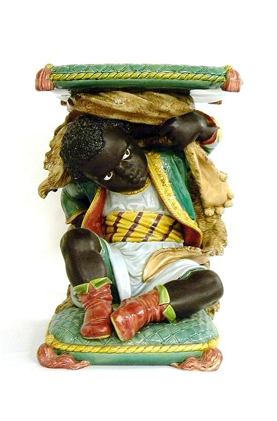 Blackamoor figure garden seat, [Minton reference no. 225 Cuniningham, p. 32 & 33], of a young boy sitting on a green tufted pillow a...