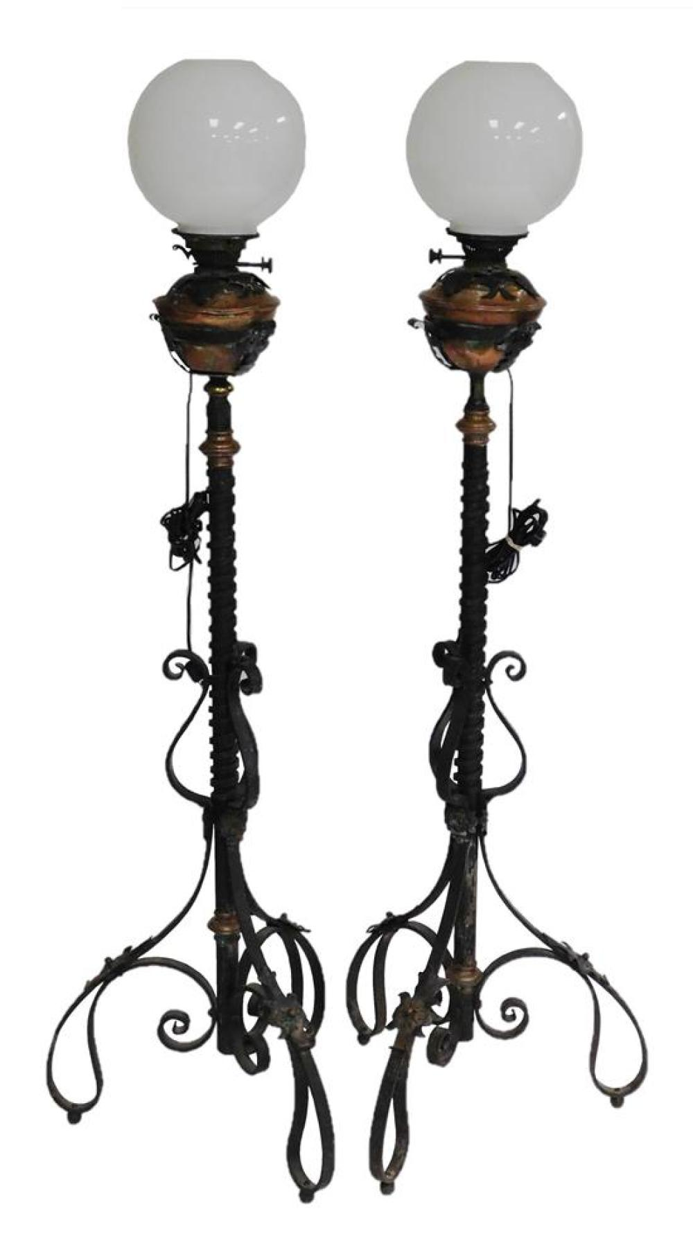 Two French standing fluid lamps, 19th C., wrought iron, copper, etc., electrified, copper font held in place by leaf form supports,...