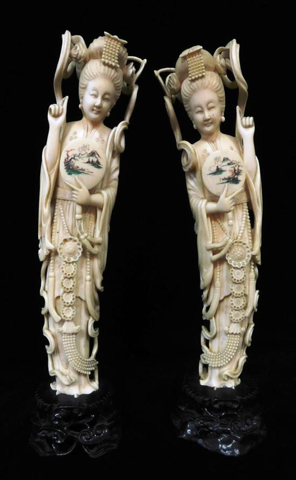 ASIAN: 20th C. Pair of ivory female deities (tusk form) holding fans with polychrome decoration, on mounted stands, wear consistent...
