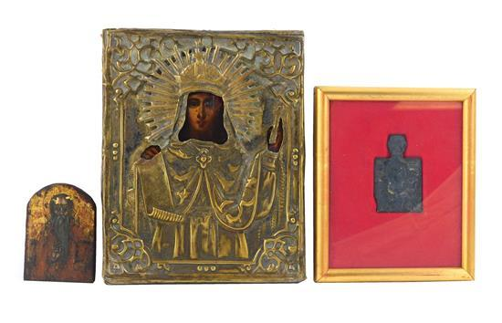 Three icons, 19th C. or earlier, one on panel with brass riza and depicting St. Paraskeva Pyatnista, one on panel with arched top an...
