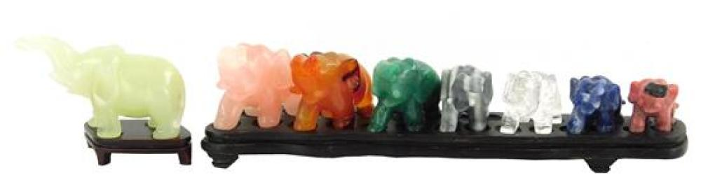 Carved hardstone elephants, eight pieces, including: seven graduated in size on fitted rosewood finish stand, stones appear to be ro...