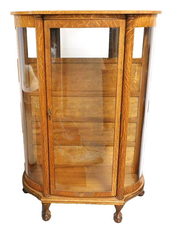 Oak curio cabinet, late 19th C., paw feet curved glass sides, column pilasters, four removable glass shelves, wear consistent with a...