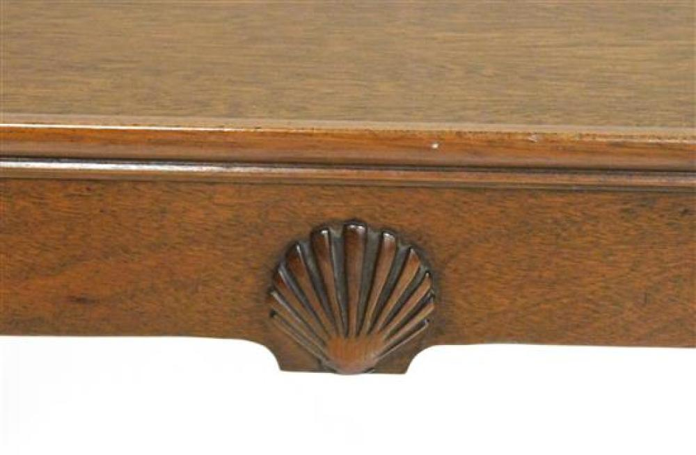 Queen Anne reproduction tea table with shell carved frieze, mahogany finish, molded edge to rectangular top, two slides, elongated c...