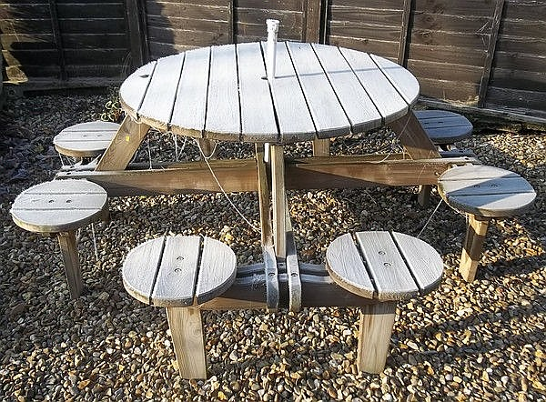An eight seater patio table with pairs of built in
