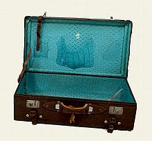 A vintage crocodile skin suitcase with bright