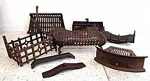 A group of five cast iron fire grates and baskets