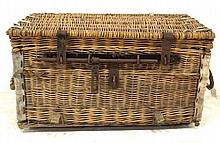 A wicker basket with leather bound corners and an