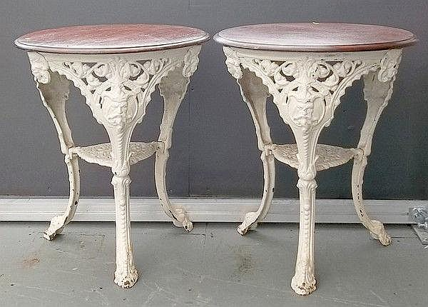 A pair of cast iron garden tables of outswept