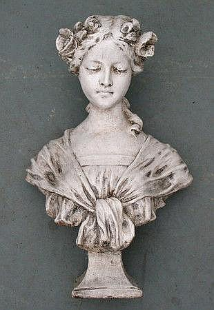 A composition stone bust of a young girl with a