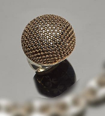 A SILVER, BRONZE AND ZIRCON RING