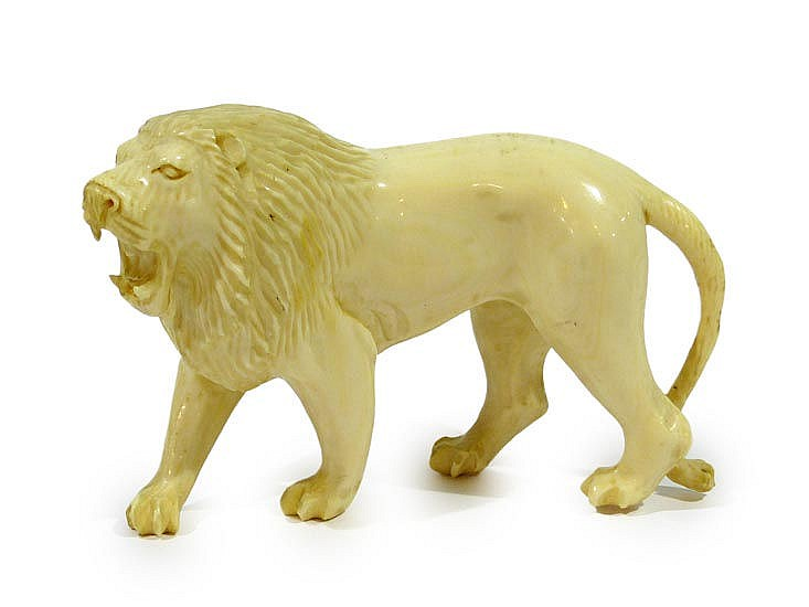 AN IVORY LION FIGURINE