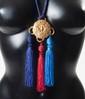 YVES SAINT LAURENT Long collier en passementerie retenant un médaillon gravé en métal doré à trois pompons rouge, bleu et violet - Longueur: 75 cm (unsigned)Long necklace made of silk rope with gold tone medallion pendant - Length: 30in. (unsigned)