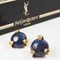 YVES SAINT LAURENT Rive Gauche Prototype Paire de clips d'oreilles ronds en métal doré centrée de deux résines bleues paillettées, porte l'étiquette du défilé n° 101 - Diamètre : 3,5 cm ( non signé)Gold tone round earclips set with blue resin rocks -
