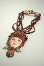 Collier en perles de verre grenat et noir à médaillon orné d'une tête de poupée en porcelaine