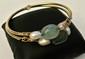 Bracelet de style antique composé de deux joncs en or centré de deux émeraudes brutes et quatre perles baroques, poids brut: 48,1 g - Gold antique style pair of bracelets, weight : 30,8 dwt