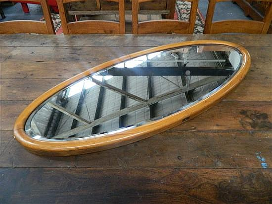 An oval beachwood bevelled glass mirror