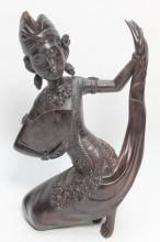 An Indonesian Carved Wood Dancer, Poised on her Knees, with her Left Arm Outstretched Lifting the Train of her Bejeweled Dress