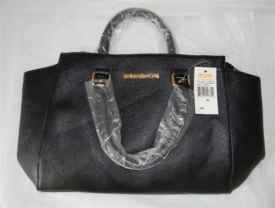 A ladies fashion hand bag marked Michael Kors in black