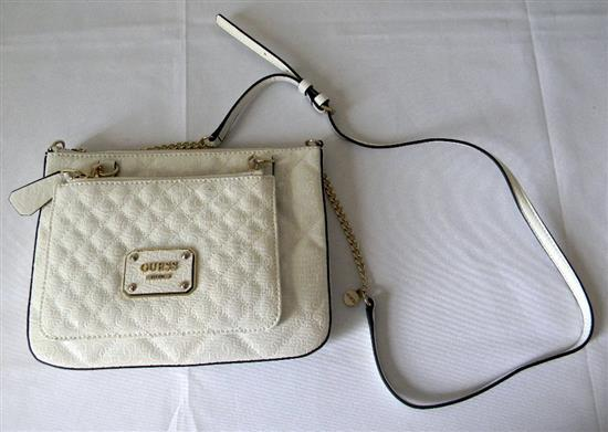 A white ladies fashion hand bag marked Guess