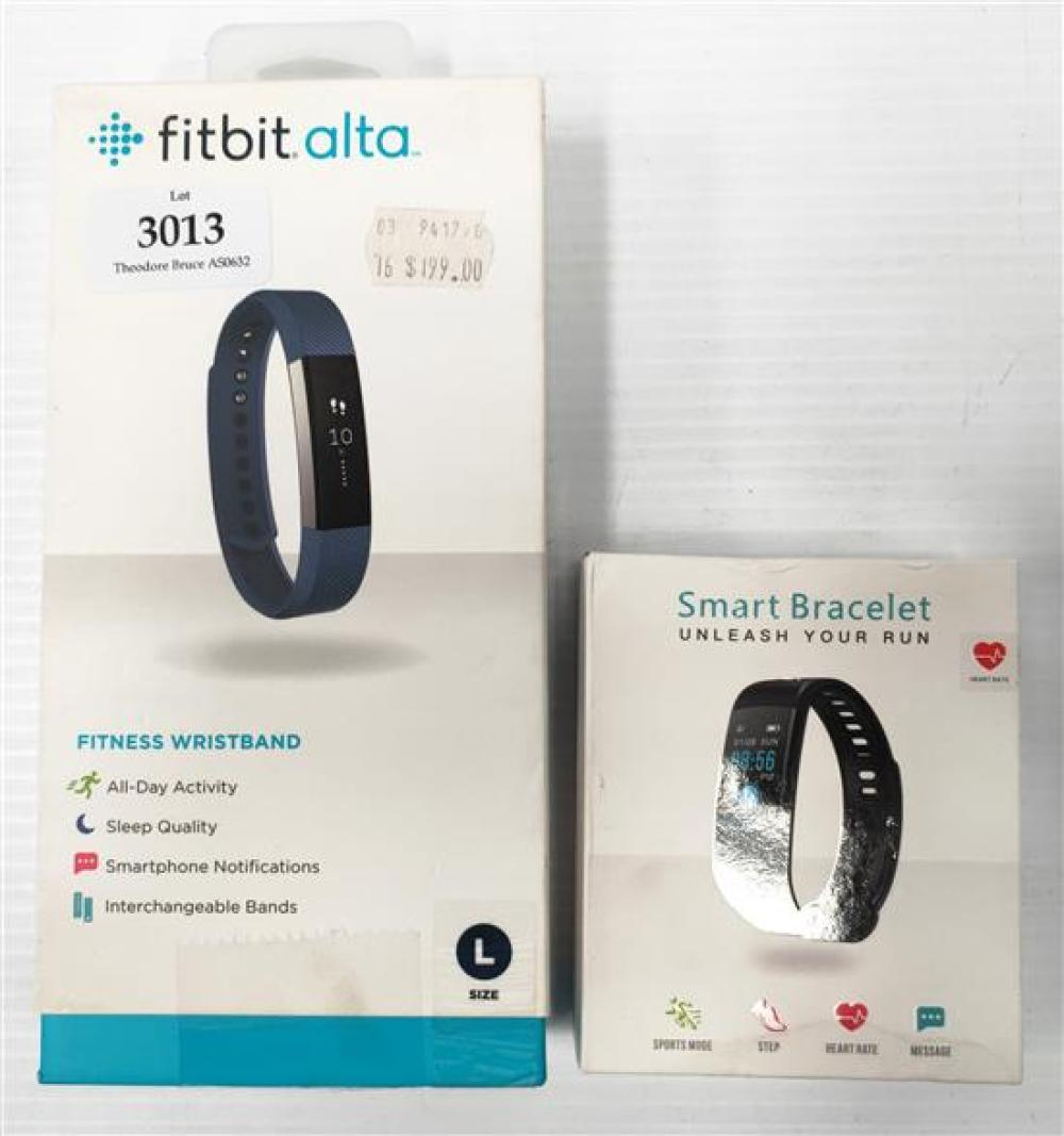 A fitness wrist band marked Fitbit Alta Size L plus another