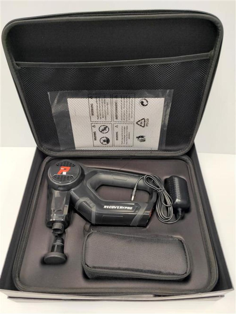 A massage gun marked Recovery Pro in open box, used