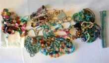 A bag of assorted enamel & stone finish costume jewellery etc.