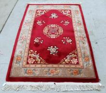 A Chinese Fringed Rug with a Central Red Mat Framed by Floral Patterning,