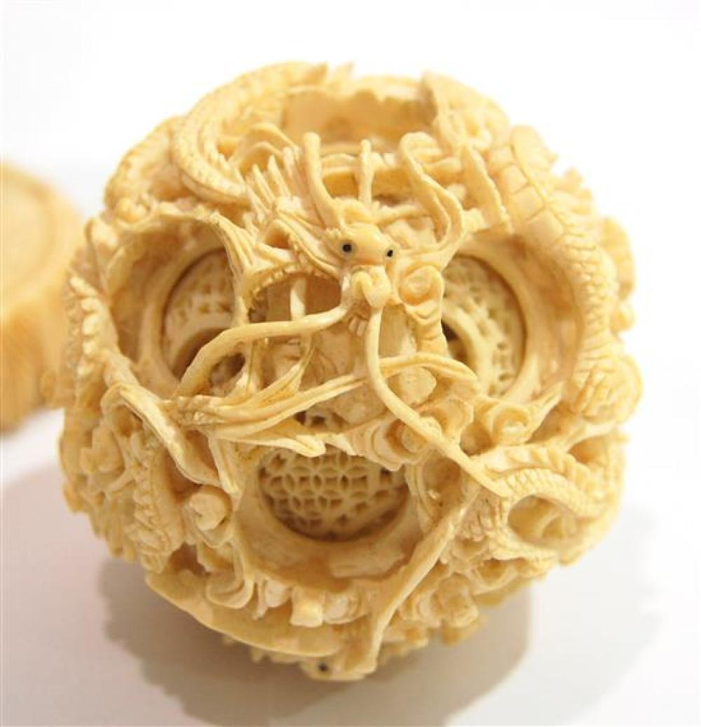 A Finely Carved Chinese Ivory Puzzle Ball Being Held Up By
