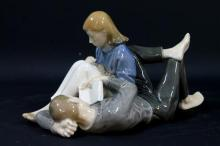 A Royal Copenhagen Figure of a Reclining Young Couple Reading