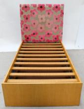 A Single Bed with Trundle Storage and a Grey and Floral Upholstered Bedhead