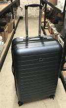 A large blue hard suitcase marked Delsey, used
