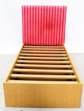 A Single Bed with Trundle Storage and Pink Striped Upholstered Bedhead